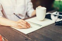 Weibliche Hand mit Bleistiftschreiben auf Notizbuch Frauenhand mit Stift Stockbilder