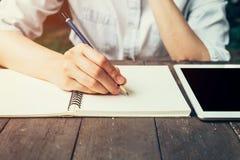Weibliche Hand mit Bleistiftschreiben auf Notizbuch Frauenhand mit Stift Lizenzfreies Stockbild