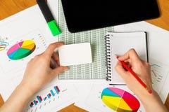 Weibliche Hand mit Bleistiftschreiben im Notizbuch auf Tischplattenhintergrund Lizenzfreies Stockbild