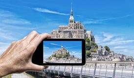 Weibliche Hand mit dem Smartphone, der ein Foto von Mont Saint Miche macht Stockfotografie