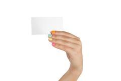 Weibliche Hand mit der mehrfarbigen Maniküre, die eine leere Visitenkarte hält Stockfotografie