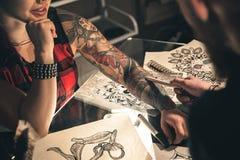 Weibliche Hand mit der Tätowierung, die auf Schreibtisch aufstellt Stockbilder