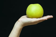Weibliche Hand mit einem grünen Apfel Stockfotografie
