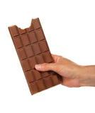 Weibliche Hand mit einer Fliese der Milchschokolade Stockfotografie