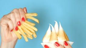 Weibliche Hand mit einer Manik?re, einen kleinen Kuchen mit Meringe und Pommes-Frites, auf einem blauen Hintergrund halten Nahauf stockbilder