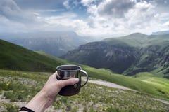 Weibliche Hand mit einer Tasse Tee auf einem Hintergrund von Bergen lizenzfreie stockfotografie