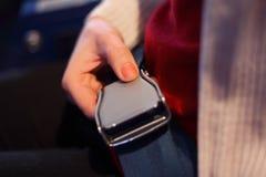 Weibliche Hand mit einer Verriegelung des Sicherheitsgurtes Stockfotos
