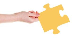 Weibliche Hand mit gelbem Puzzlespielstück Lizenzfreies Stockfoto
