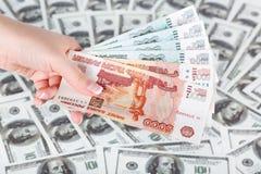 Weibliche Hand mit Gruppe von Rubeln auf einem Hintergrund von Dollar Lizenzfreie Stockbilder