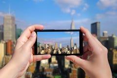 Weibliche Hand mit Handy machen Foto der Stadtmitte von Manhattan auf Sonnenuntergang Panorama von Wolkenkratzern von New York Ci Stockfotografie