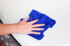 Weibliche Hand mit sauberem weißem Auto microfiber Stoffes Stockfotografie