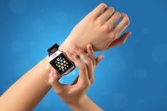 Weibliche Hand mit smartwatch und APP-Ikonen Stockbilder