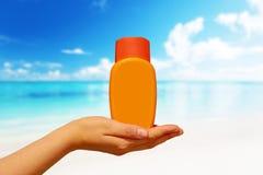 Weibliche Hand mit suncream Flaschenhintergrund-Blauhimmel Lizenzfreie Stockbilder