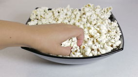 Weibliche Hand nimmt das Popcorn von einer Platte stock video