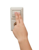 Weibliche Hand schaltet das Licht ein Stockfoto