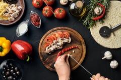 Weibliche Hand schnitt Knoblauch, Paprikas, Pilze und Tomaten auf hölzernem Brett auf Küchentisch, um Lügenbestandteile für stockbilder