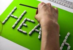 Weibliche Hand setzt die Wortgesundheit auf einen grünen Hintergrund Weiße Tabletten, das Konzept eines gesunden Lebensstils lizenzfreie stockfotos