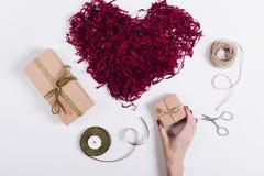 Weibliche Hand setzt Kästen mit Geschenken nahe einem roten dekorativen Herzen Lizenzfreie Stockfotografie