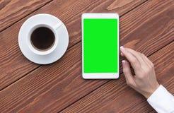 Weibliche Hand unter Verwendung der digitalen Tablette und des Tasse Kaffees des Modells auf braunem hölzernem Schreibtisch, Drau lizenzfreies stockbild