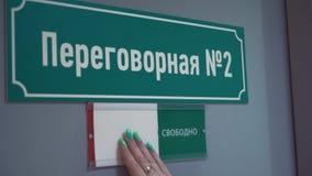 Weibliche Hand verschiebt Platte auf besetzt auf Tür mit kyrillischem TextKonferenzzimmer stock video footage
