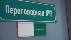 Weibliche Hand verschiebt Platte auf besetzt auf Tür mit russischem TextKonferenzzimmer stock video