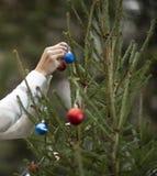 Weibliche Hand verziert den Weihnachtsbaum lizenzfreies stockbild