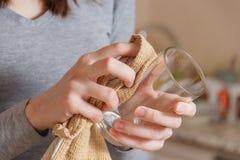 Weibliche Hand wischt sauberes Glas durch Hahn in der Küche ab Hausarbeit, Spring Cleaning Konzept Stockfotografie