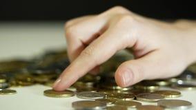 Weibliche Hand zählt die Münzen auf dem Tisch stock footage