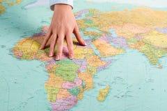Weibliche Hand zeigt afrikanischen Kontinent stockbild