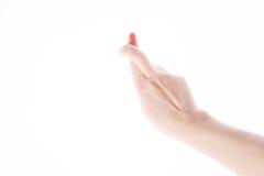 Weibliche Hand zeigt Zeichen des guten Glücks auf einem Weiß Stockfoto