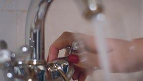 Weibliche Handdrehengriff auf Hahn und strömendes Wasser in Glas im Badezimmer stock footage