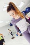 Weibliche Handelnstepp-aerobic in der Turnhalle Stockbilder