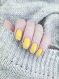 Weibliche Handentspannen sich gelber Maniküreschönheits-Strickjackensalon Winterdekoration lizenzfreies stockfoto