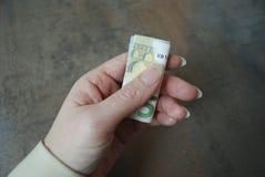 Weibliche Handgriffe falteten Währungsbanknote Stockfoto
