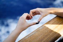 Weibliche Handherzform, die nach hölzernem Brett hält Natur bokeh Sonnenlichtwelle und blauer Wellenhintergrund lizenzfreie stockfotos
