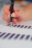 Weibliche Handholdingfeder über Geschäftsdiagramm Lizenzfreie Stockbilder