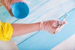 Weibliche Handnahaufnahme von gemalten Planken in der blauen Farbe holzarbeit fertigkeit stockfotos