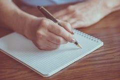 Weibliche Handschrift auf Notizbuch stockfotografie