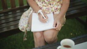 Weibliche Handschrift ein Buchstabe auf dem Papier auf dem Akt bräunte sich Knie stock video