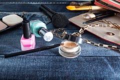 Weibliche Handtasche mit Kosmetik und Mobile auf Jeanshintergrund Lizenzfreies Stockbild