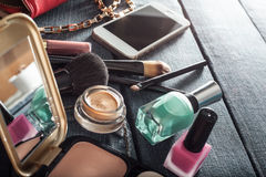 Weibliche Handtasche mit Kosmetik und Mobile auf Jeanshintergrund Stockfotografie