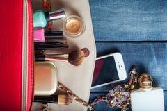 Weibliche Handtasche mit Kosmetik und Mobile auf Jeanshintergrund Stockfoto