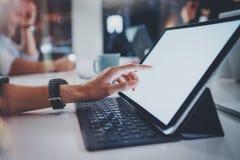 Weibliche Handtouch Screen der elektronischen Tablette mit Tastaturdockstation Nachtam modernen Bürodachboden verwischt Stockbild