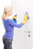 Weibliche Haushälterin, die eine Tür säubert Stockbild