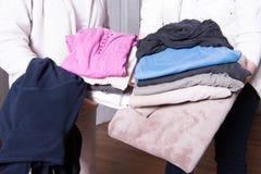 Weibliche Helfer bieten warme Kleidung Flüchtlingen an Stockfotografie