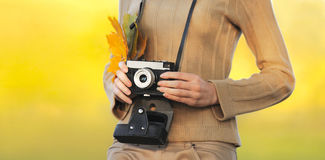 Weibliche Hände des Herbstfotos, die Retro- Weinlesekamera mit gelber Ahornblattnahaufnahme in sonnigem warmem Tag halten Stockfoto