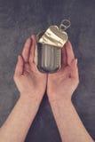 Weibliche Hände, die offene leere Sardinen-Fische Tin Can halten Stockfotos