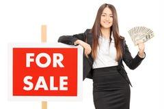 Weibliche Immobilienagentur, die Geld durch a für Verkaufszeichen hält Lizenzfreie Stockbilder