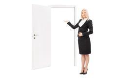 Weibliche Immobilienagentur, die in Richtung zu einer Tür zeigt Lizenzfreies Stockbild