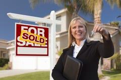 Weibliche Immobilienagentur Handing Over die Haus-Schlüssel Stockfotos